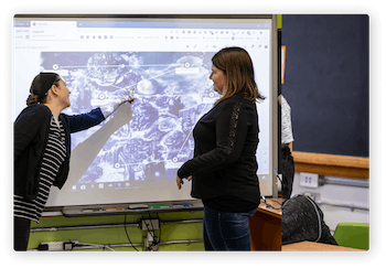Teacher and student in front of the class pointing something on the interactive board
