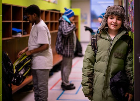 Middle schooler in a winter hat and jacket smiling while standing in a school hallway