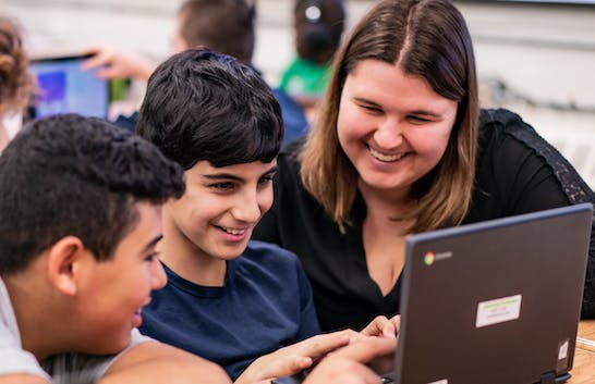 Teacher with two students looking to a chromebook at their desk